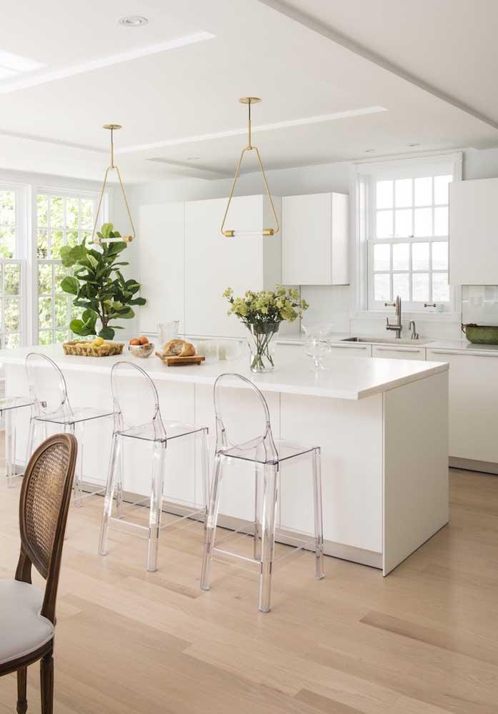 Cozinha branca e clean com banquetas de acrílico servindo à ilha central