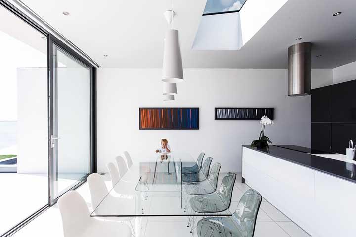 Sala de jantar moderna e elegante com mesa de vidro e composição de cadeiras Eames Eiffel de acrílico e de plástico branco