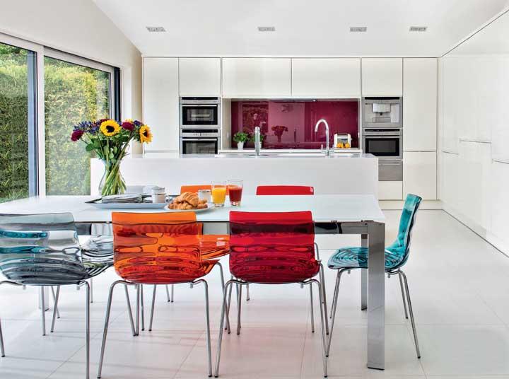 A cozinha de base branca ficou perfeita com a combinação de cadeiras de acrílico em três cores diferentes