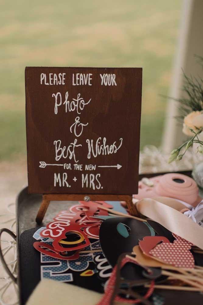 As plaquinhas de casamento dão as instruções para as fotos nessa festa