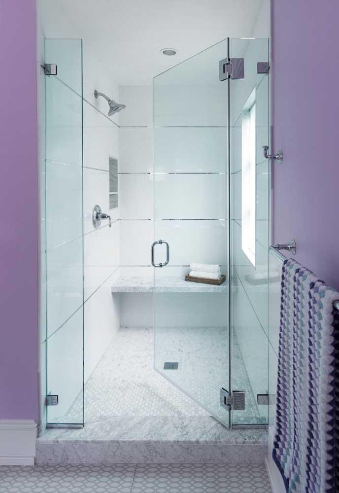 Para proporcionar um ambiente mais equilibrado, você pode usar os azulejos na cor branca na área do box e pintar a parede do banheiro na cor roxa clara.