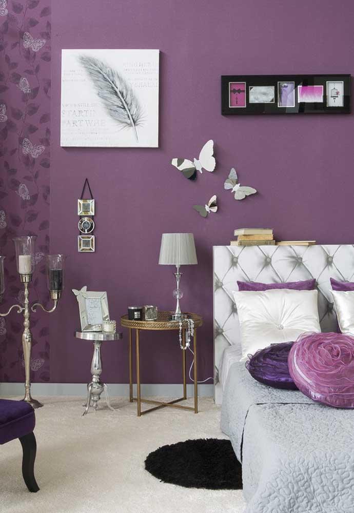 Use alguns itens decorativos mais clássicos na hora de decorar o quarto com a parede na cor roxa.