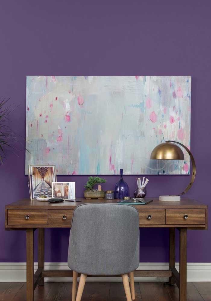 Os móveis de madeira também combinam com a parede na cor roxa.