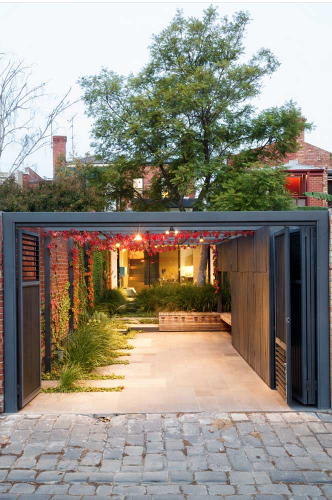 A garagem dessa casa com pergolado ganhou uma linda cobertura de hera americana, o diferencial dessa espécie são as folhas que mudam de cor, indo do verde ao avermelhado