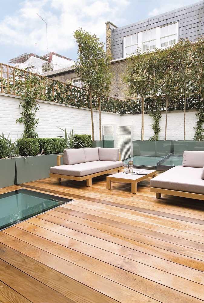Nesse quintal moderno, a planta trepadeira encontra, ao final do muro, uma treliça de madeira para se agarrar