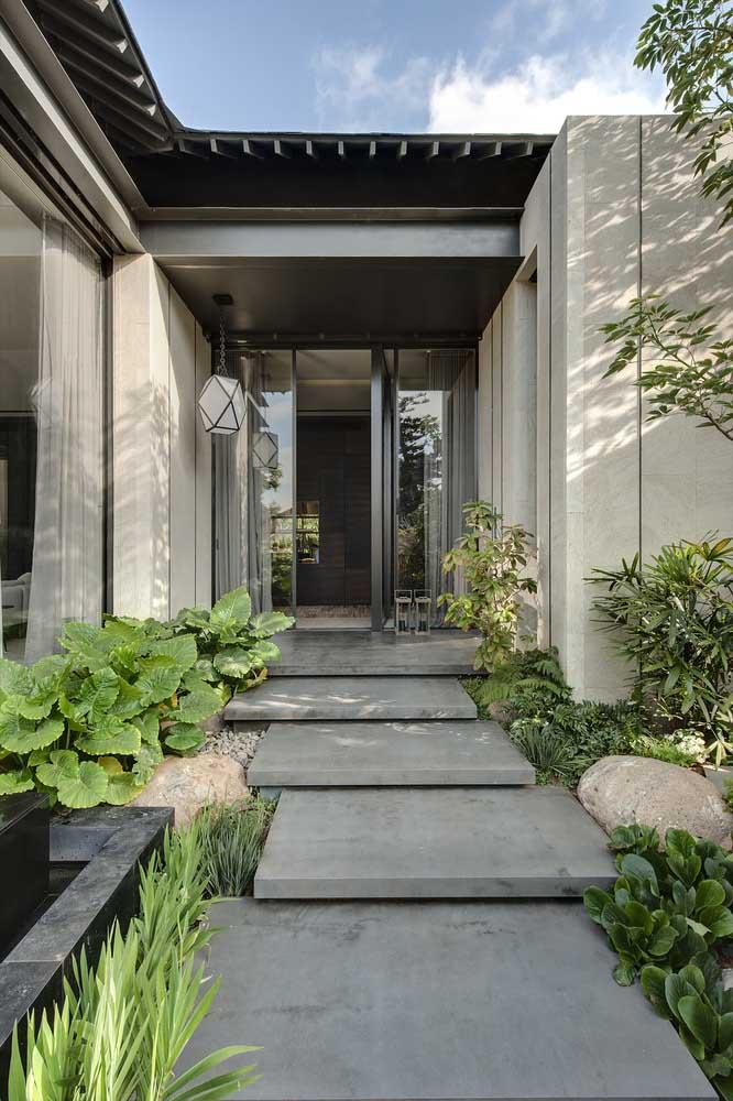 Entrada da casa contornada por um jardim moderno pequeno com pedras e fonte ao lado