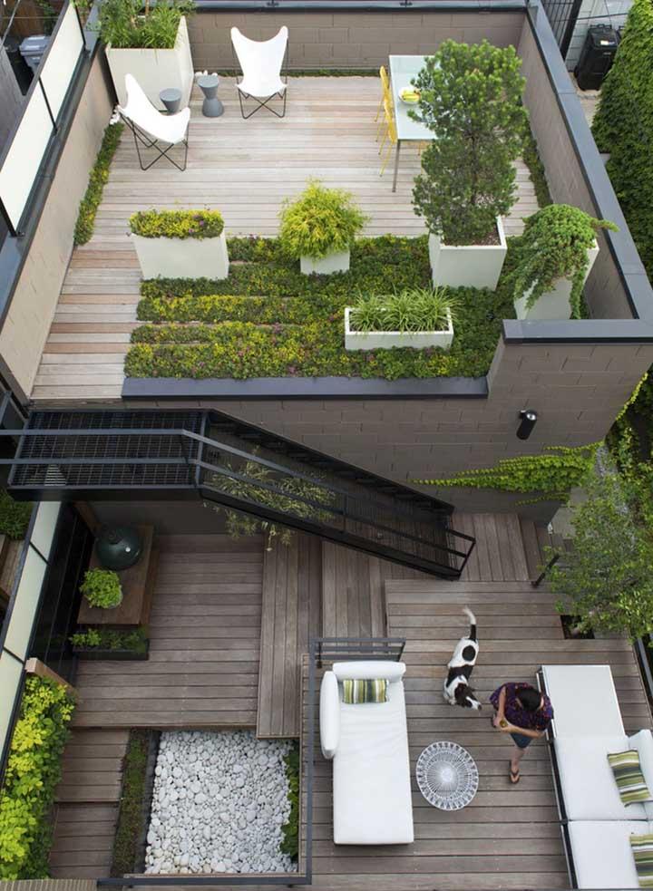 Um jardim moderno visto de cima, com piso em madeira e móveis contemporâneos, além dos vasos grandes e brancos