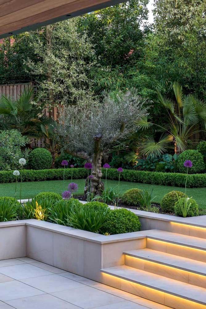 Esse jardim moderno trouxe muito verde para a casa, com palmeiras aos fundos e plantas pequenas envolvendo a escada com iluminação em LED