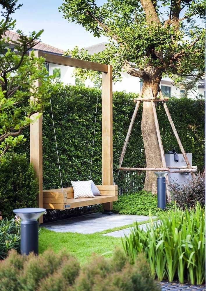 Esse jardim moderno é mais que convidativo; o balanço em madeira complementou o ambiente cheio de verde
