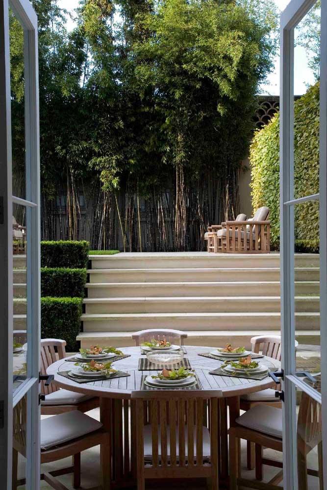 A varanda gourmet contou com a vista deslumbrante do jardim moderno, decorado com bambus e poltronas em madeira
