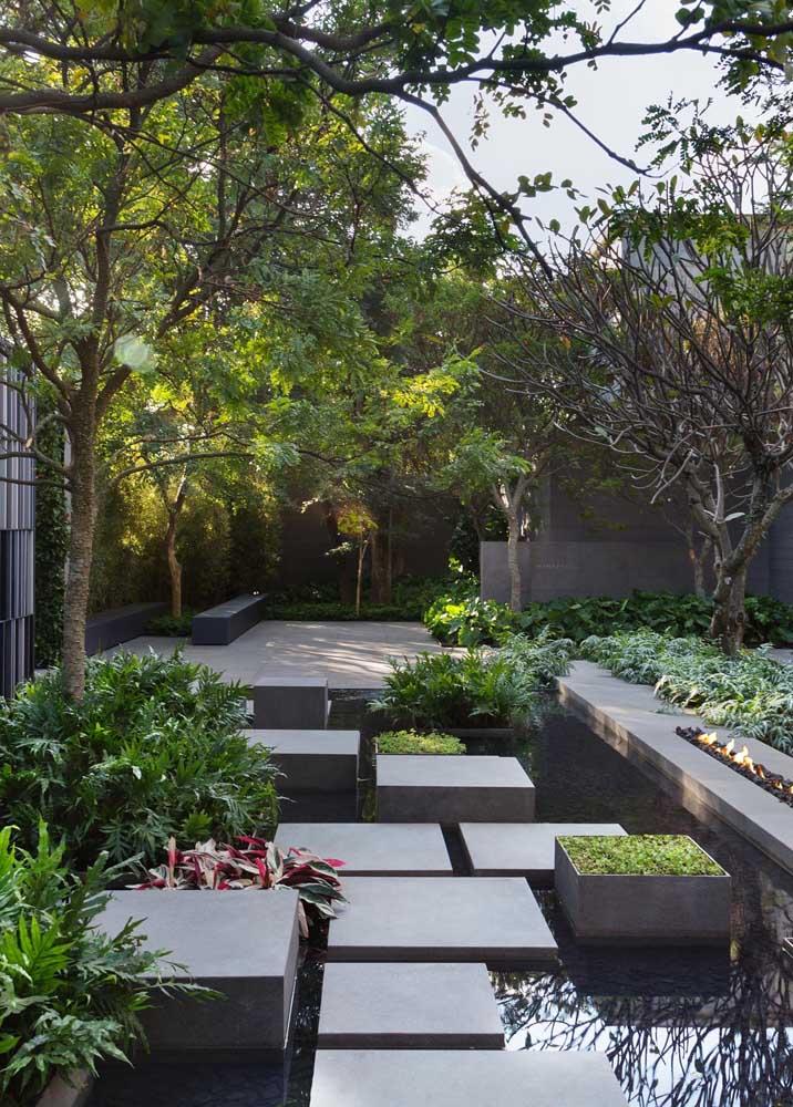 O lago artificial ficou perfeito com o caminho criado em alvenaria para alcançar o outro lado do jardim moderno