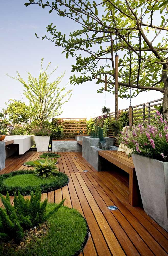 Piso em madeira e gramado nos pequenos canteiros demarcados no centro desse jardim moderno