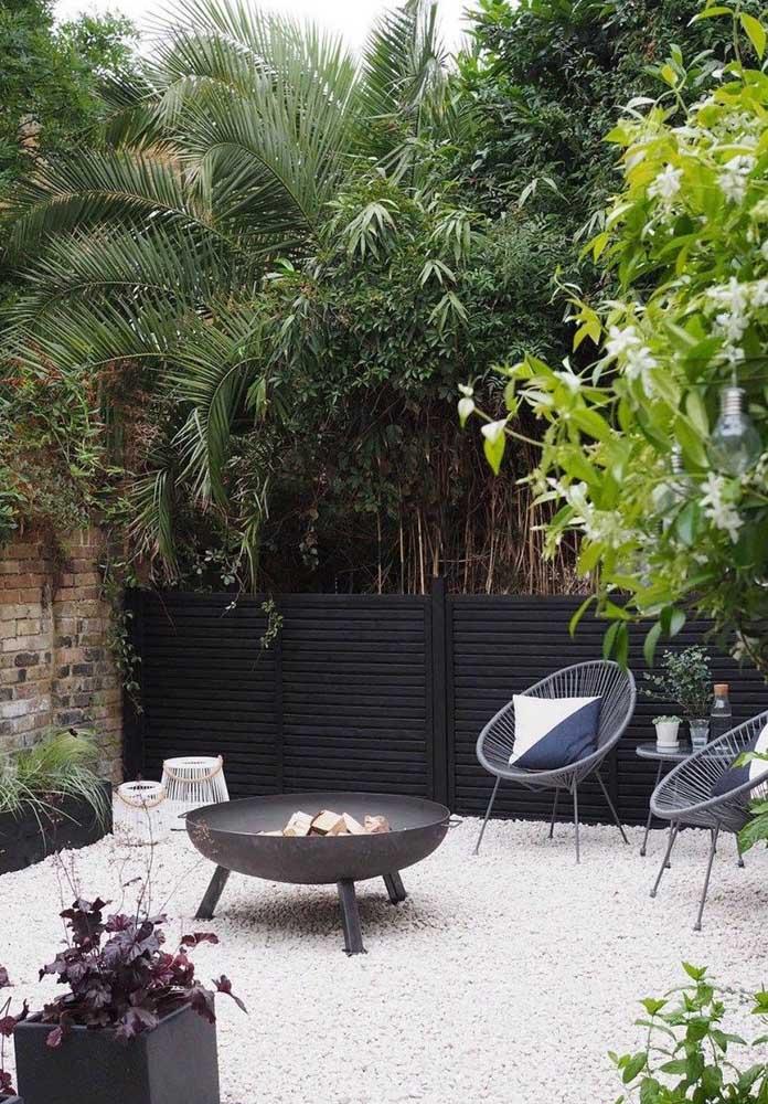 Esse jardim moderno ganhou pedregulhos para completar sua base, com móveis contemporâneos, palmeiras e uma charmosa fogueira ao centro