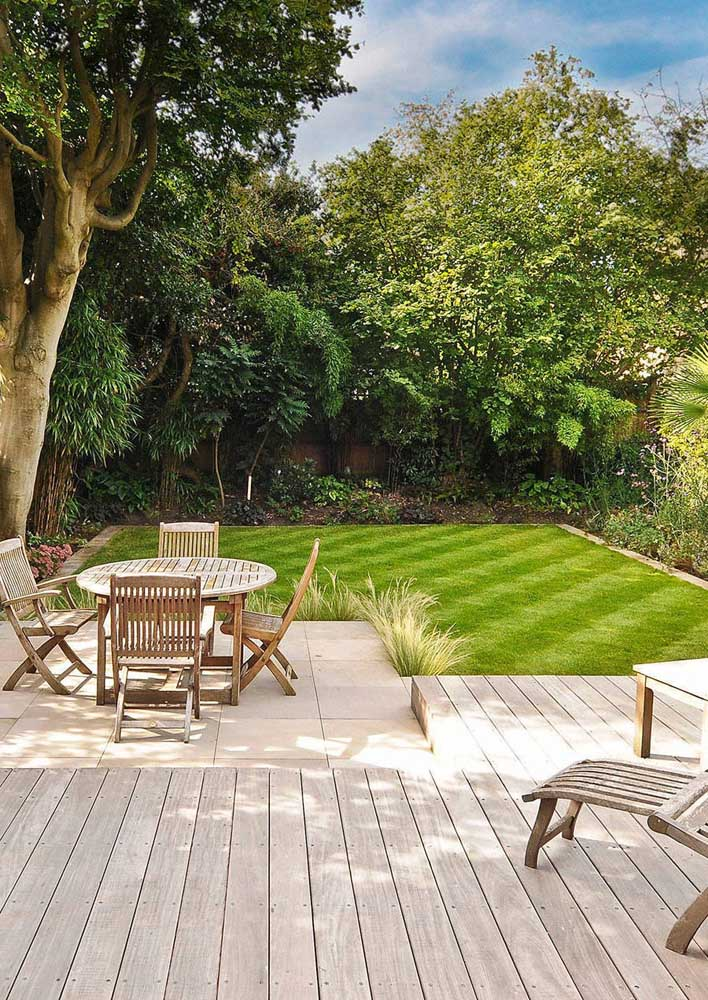 Jardim moderno minimalista com amplo gramado e móveis em madeira