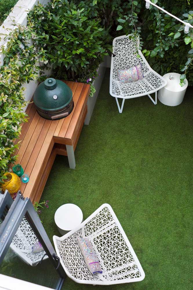 Jardim moderno pequeno com móveis brancos e bancada em madeira