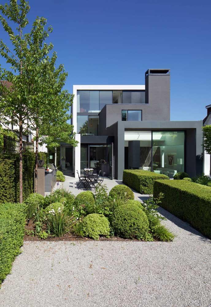 A fachada desta casa contemporânea ficou perfeita com a inclusão do jardim moderno e o chão forrado de pedras