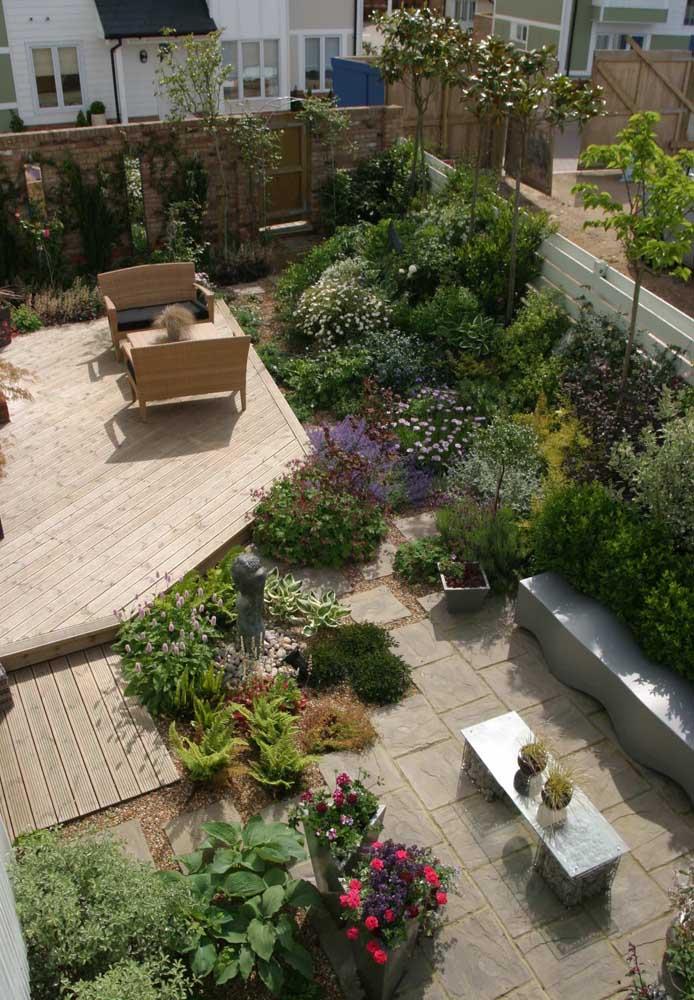 Um jardim moderno visto de cima, com vasos e canteiros ricos em verde, além dos móveis em madeira e alvenaria.