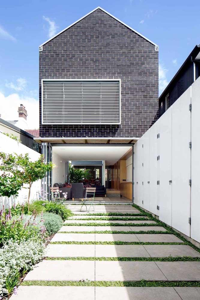 Para os fundos desta residência foi escolhido um pequeno canteiro verde enchendo o espaço de beleza e vida