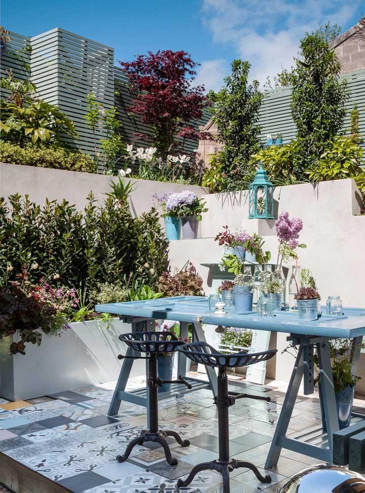 Jardim moderno pequeno com detalhes em azul e canteiro de plantas; ideal para varandas de apartamento