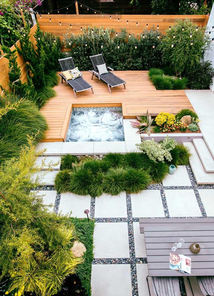 Jardim moderno com lago artificial simples e placas em alvenaria contracenando com o piso em madeira