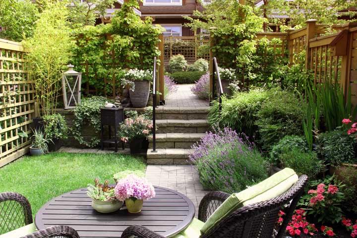 Esse jardim pequeno e acolhedor ganhou peças em madeira e muito verde ao redor