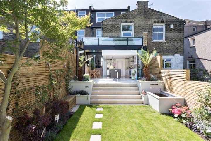 Jardim moderno aos fundos da casa com campo gramado e muros em madeira, rodeados por plantas pequenas e delicadas