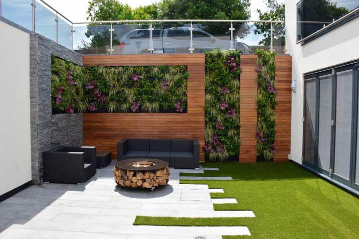 Jardim vertical entre o painel de madeira; ao lado, a fogueira social perfeita para momentos em família