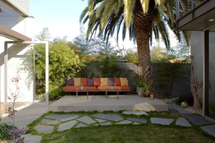 A grande palmeira fez companhia para o sofá colorido no jardim moderno da casa