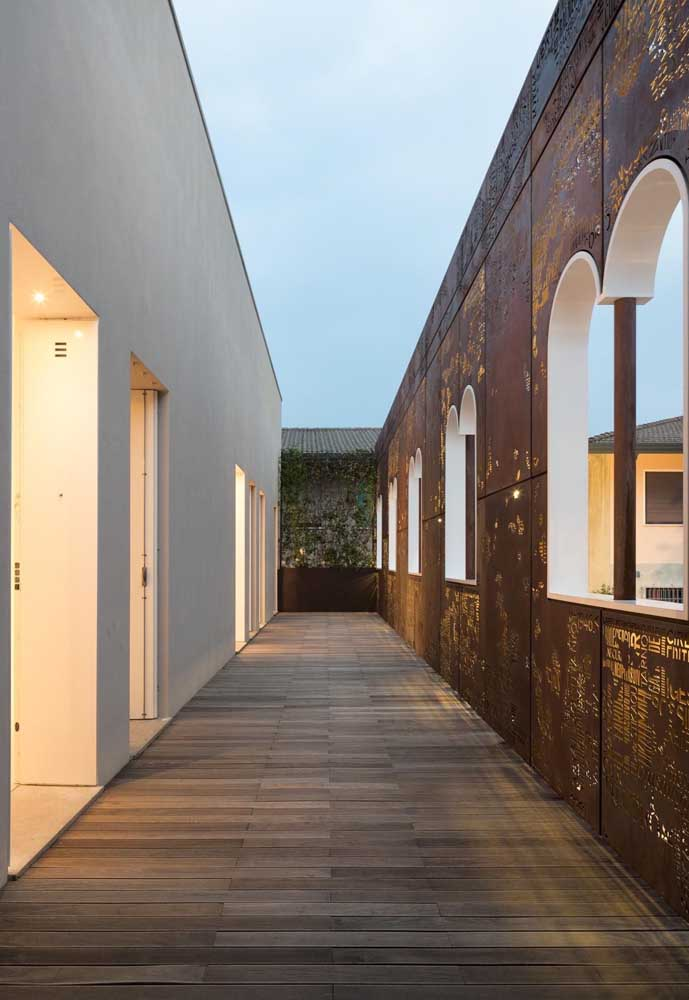 A parede externa adornada por arcos recebeu a intervenção contemporânea das chapas de aço corten