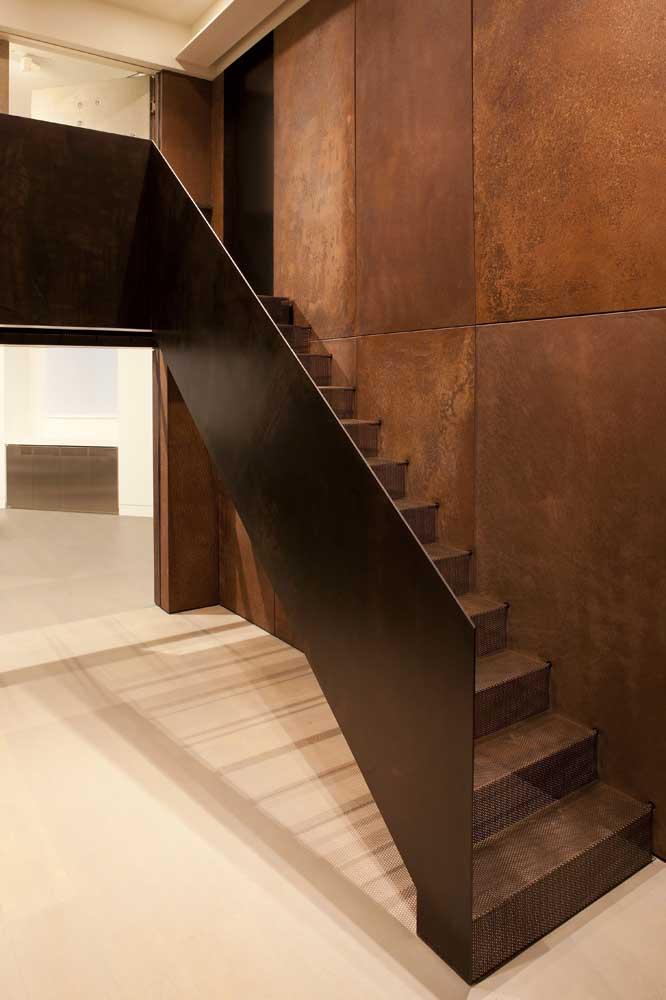 No interior dessa residência, o aço corten aparece na parede, no guarda corpo da escada e nos degraus