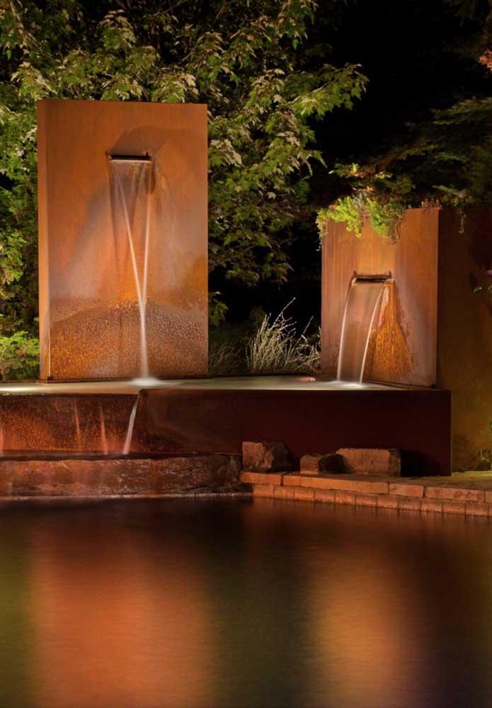Junto à piscina, o aço corten forma o suporte para criação da cascata de água