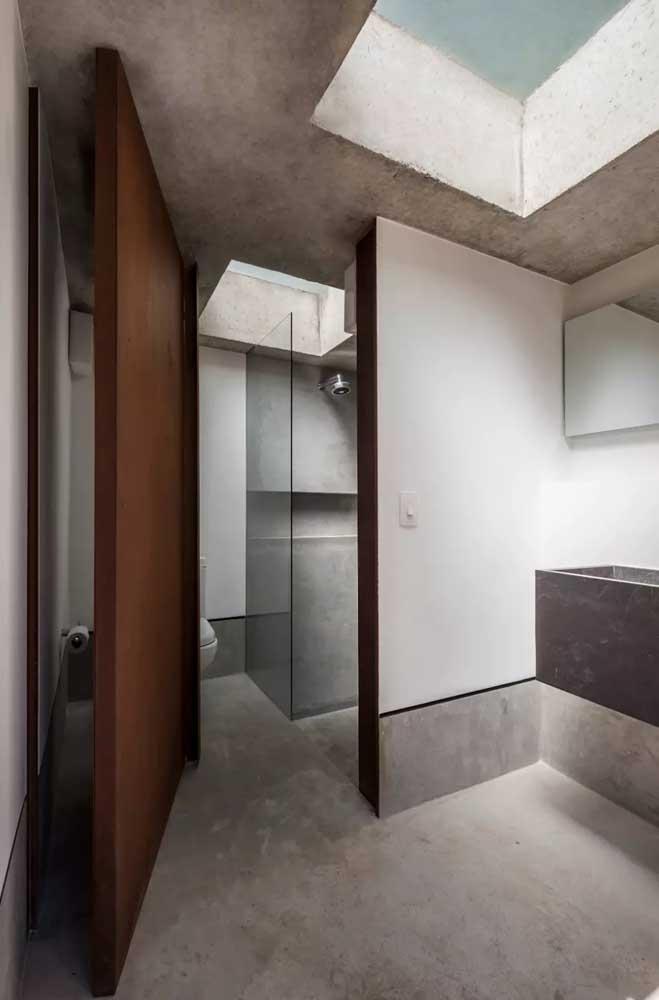 E o que acha desse banheiro com porta em aço corten? O modelo pivotante combinado ao uso do cimento queimado deixou o ambiente super contemporâneo