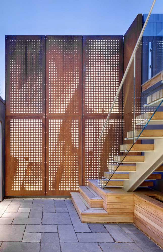 Nessa área externa, o painel vazado de aço corten atua como uma divisória de espaços