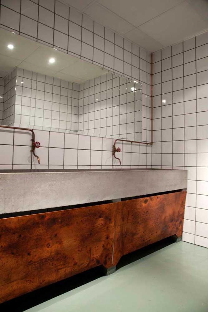 Banheiro de estilo industrial com bancada fechada por aço corten