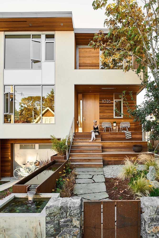 A fachada dessa casa mescla a naturalidade da madeira com a rusticidade do aço corten