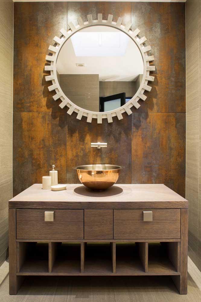 A parede da pia do banheiro ganhou revestimento em aço corten; para combinar com o tom enferrujado do material, uma cuba em tom de cobre
