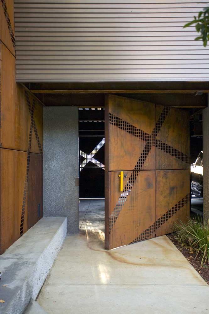 Fachada moderna com porta de aço corten em modelo pivotante; destaque para o puxador amarelo