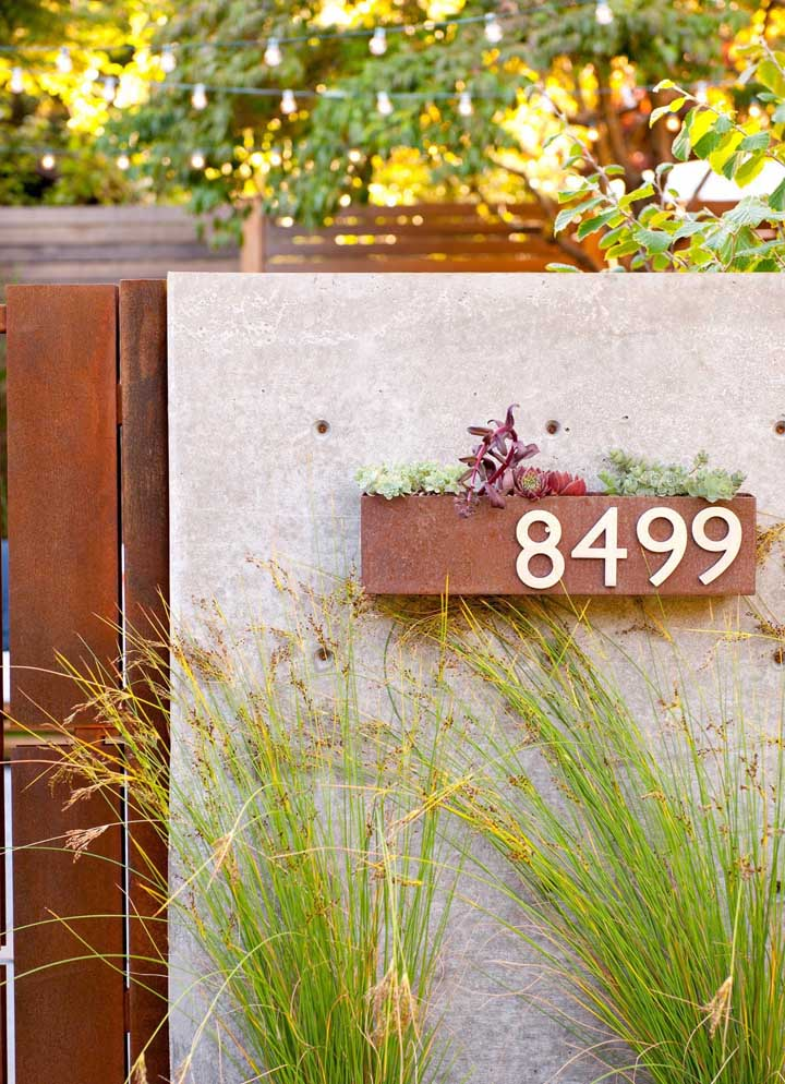 Aqui, o pequeno suporte para plantas em aço corten também serve como apoio para o número da casa