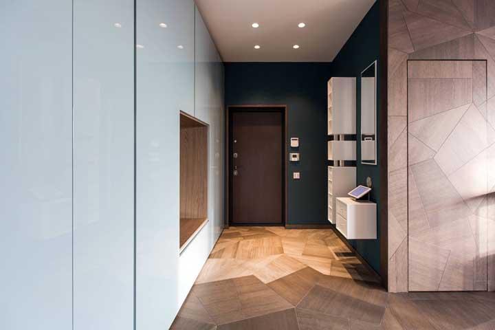 Porta, piso e parede compartilham o mesmo trabalho em marchetaria nesse hall de entrada