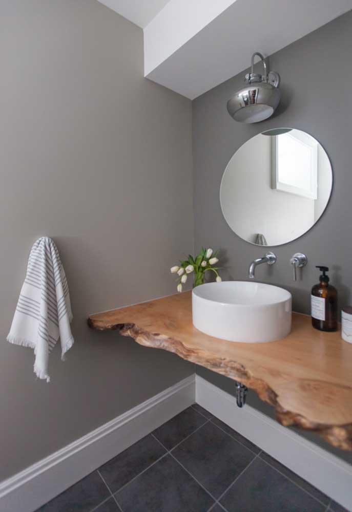 Bancada para pia de banheiro em madeira de demolição; repare que ela mantem o formato orgânico e a cor natural da peça