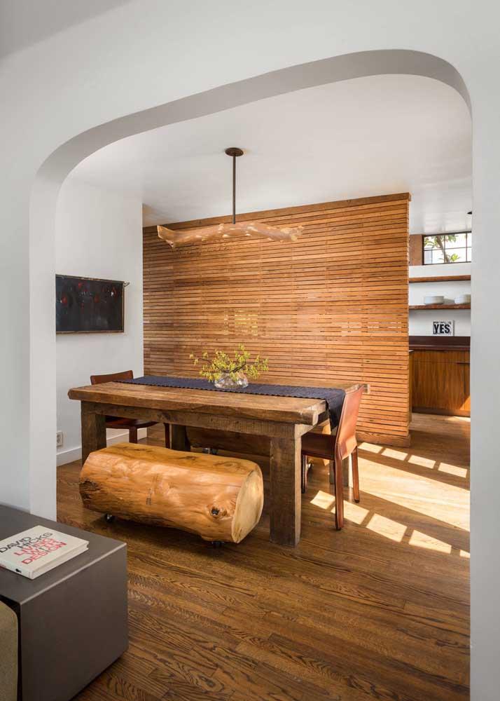 Sala de jantar com mesa e bancos em madeira de demolição combinando com o lustre e o painel ao fundo do ambiente