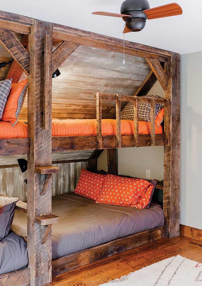 Quarto jovem com cara de acampamento graças ao estilo rústico dos beliches feitos em madeira de demolição
