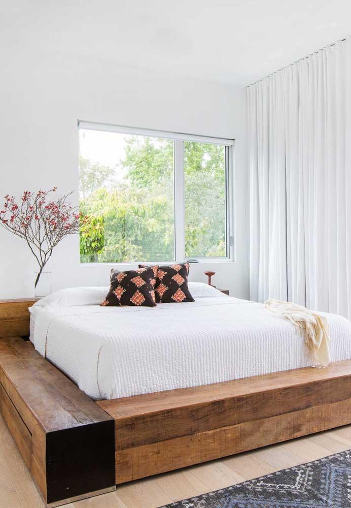 Aqui, o suporte da cama do casal foi feito em madeira de demolição envernizada