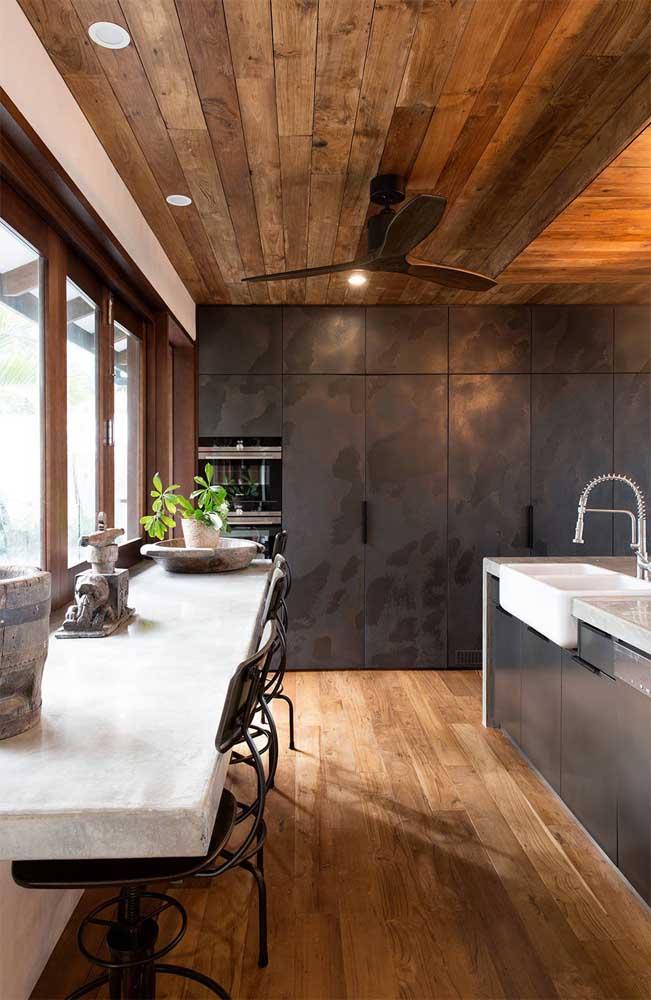 Cozinha moderna com piso e teto revestidos em madeira de demolição