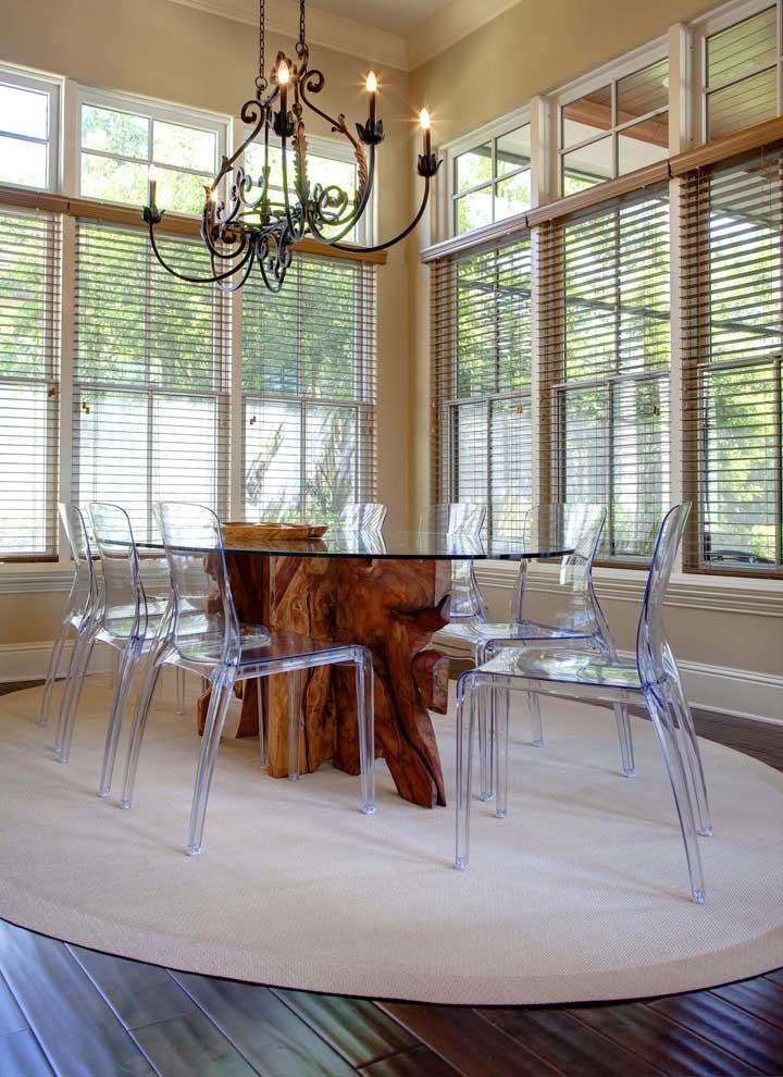 A delicadeza do vidro e das cadeiras de acrílico se contrasta lindamente com a base da mesa em madeira de demolição