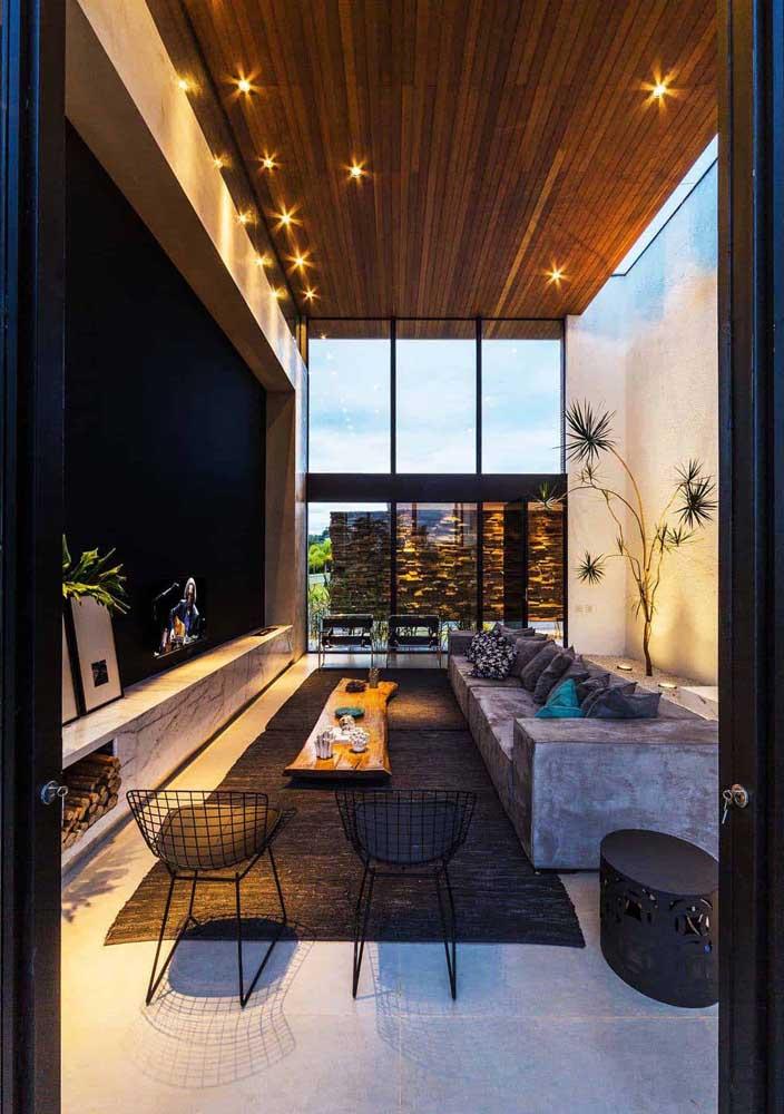 Nessa sala de estar, a madeira de demolição é a responsável por valorizar o pé direito alto