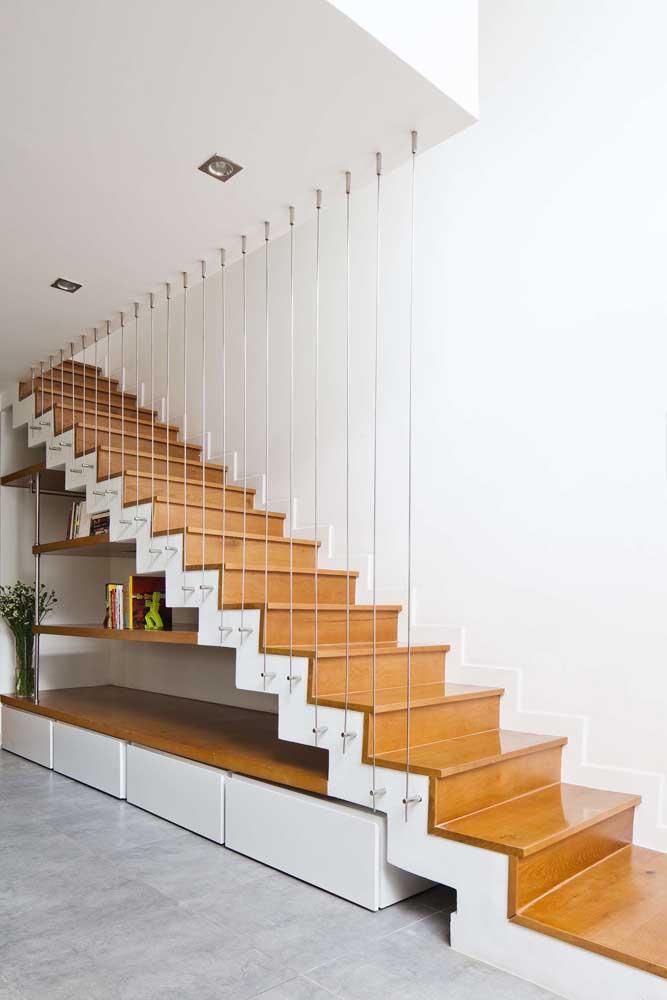 Um cantinho aconchegante embaixo da escada que pode ser usado como espaço de leitura; repare nos gavetões seguindo o mesmo padrão visual da escada