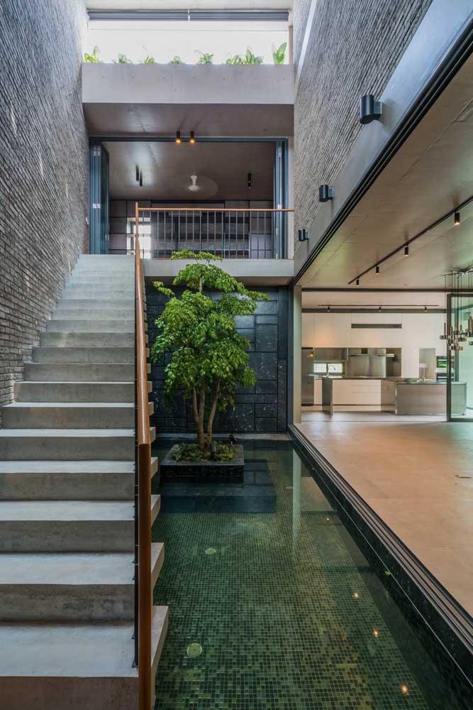 O espaço embaixo dessa escada externa foi aproveitado para a criação de um mini lago, excelente ideia, não é mesmo?