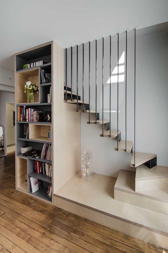 Aqui, o espaço embaixo da escada foi usado para criação de uma estante de livros