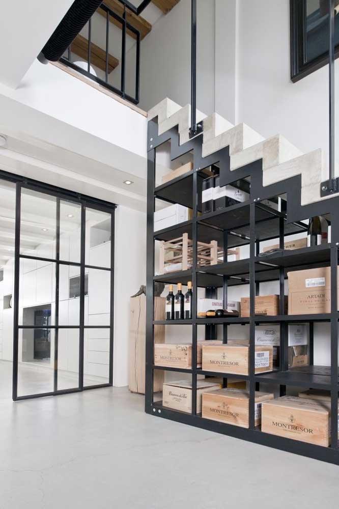Um porta trecos gigante embaixo da escada; repare na harmonia criada com os materiais utilizados: concreto na estrutura e ferro para a estante
